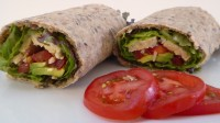 Image shows a wrap that has no refined carbs, gluten, dairy, or soy, stuffed with avocado, tempeh, lettuce, and tomato, as described in this recipe on CALMERme.com