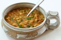 Image shows a bowl of Moroccan spiced soup with leafy greens as described in this recipe on CALMERme.com