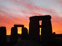 Image shows Stonehenge at sunrise as an example of a bucket list item, along with routine colonoscopies as described in this article on CALMERme.com