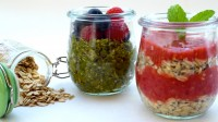 Image shows two small glass pots, one containing green tea oatmeal with berries, the other containing layers of raspberry and strawberry smoothie and oatmeal, illustrating the recipe on CALMERme.com