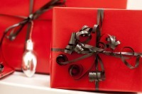 Image shows gifts wrapped in red paper and tied with a brown ribbon, to represent gifts described in this post on CALMERme.com